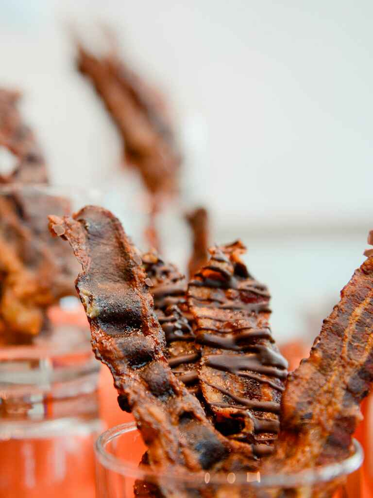 Servings of strips of bacon drizzled in chocolate at a wedding reception