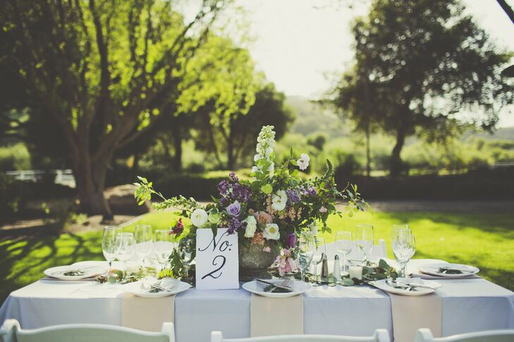 Overgrown floral centerpieces, classic calligraphed table numbers and a makeshift table runner of eucalyptus leaves perfectly fit the vineyard venue.
