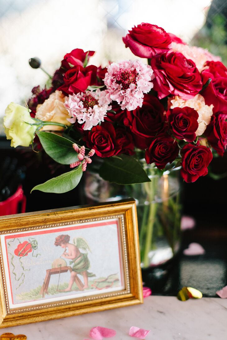 "The couple embraced a vibrant Valentine's Day motif for their big day. ""One of our favorite details was the vintage, framed Valentine's Day postcards,"" Allison says. ""They each featured cartoon cupid's delivering love letters. Some of the postcards were over 100 years old!"""