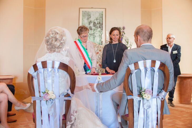 Marleen and Jasper sit in white decorated chairs front of officiants conducting their marriage ceremony in Italy.