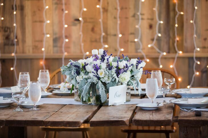Guests sat at wooden dining tables marked with simple white and gray numbers for the reception at Jorgensen Farms in Westerville, Ohio. Lush centerpieces filled with lavender, purple tulips and dusty miller decorated the dining tables.