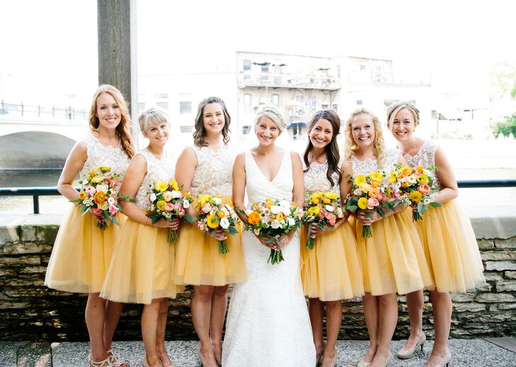 The bridesmaids wore knee-length yellow and white dresses for the retro homespun barn wedding. Katie loved the flowing tulle skirts and chic lace bodices. Each of the women chose their own nude shoes and their hairstyle for the day for a little personalization on the otherwise uniform look.
