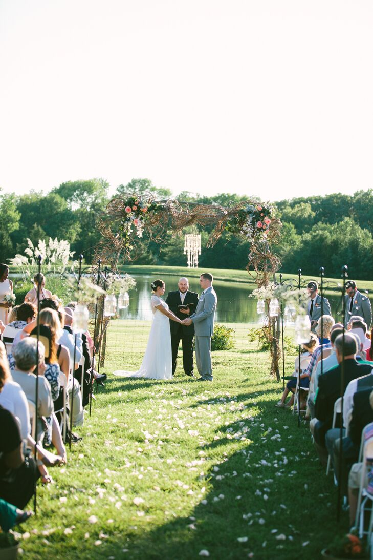 Lauren and Carter exchanged vows on the expansive lawn of Carter's family home. The spot offered beautiful views of the pond in the distance, as well as acres of lush forest. A simple vine and branch arch was constructed for the affair, with small chandelier and peach blooms adding a decorative touch to the site.