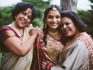 Bride with mother and grandmother in crimson and gold wedding saris