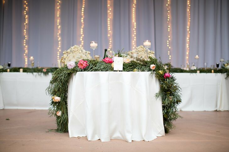 For the reception, the space was outfitted with vertical strands of twinkle lights and garland runners on tables. The sweetheart table had a floral and garland runner.