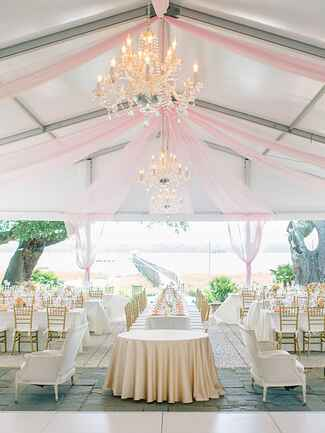 Outdoor tented wedding reception with draped ceilings and chandeliers