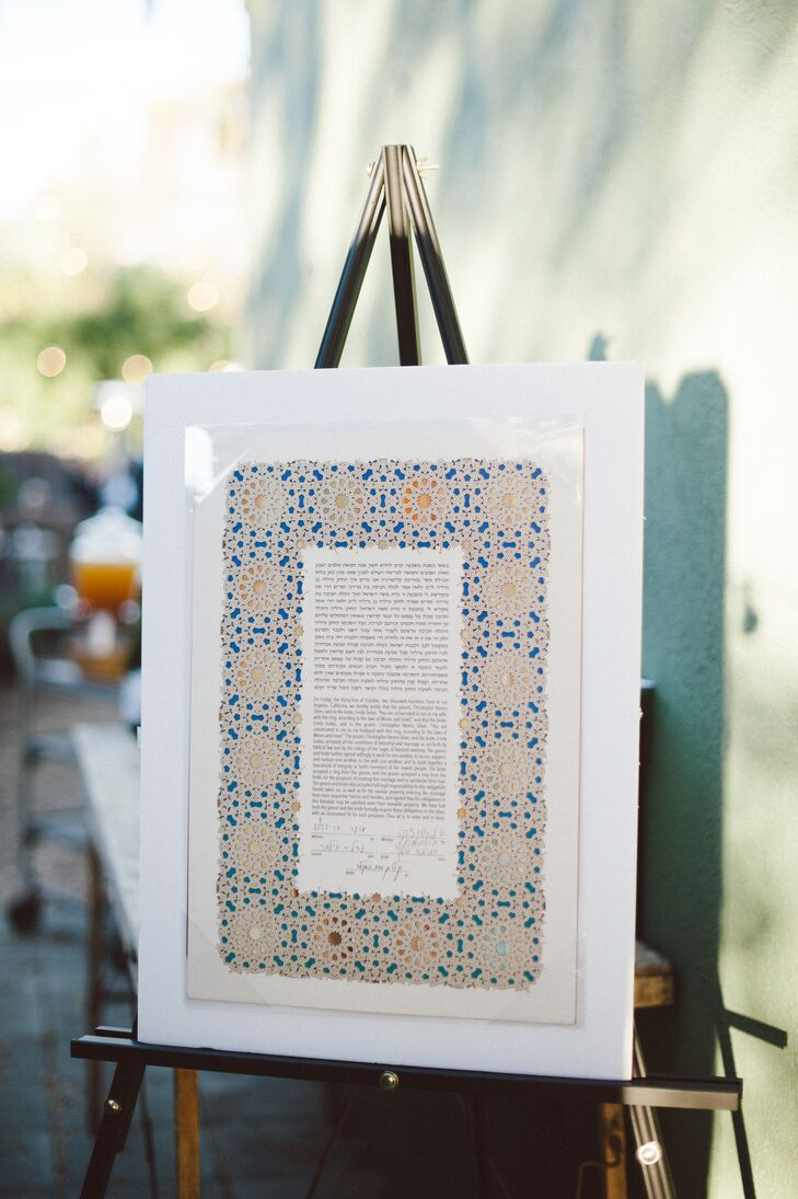 Emily and Chris signed the ketubah before their outdoor ceremony, making them officially married. The ketubah was bordered by a brown-and-blue-tiled pattern that was encased in a white frame, which was on display for the rest of the day.