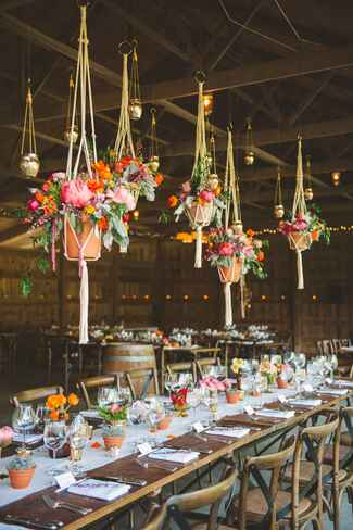 Suspended floral arrangements in a barn wedding reception