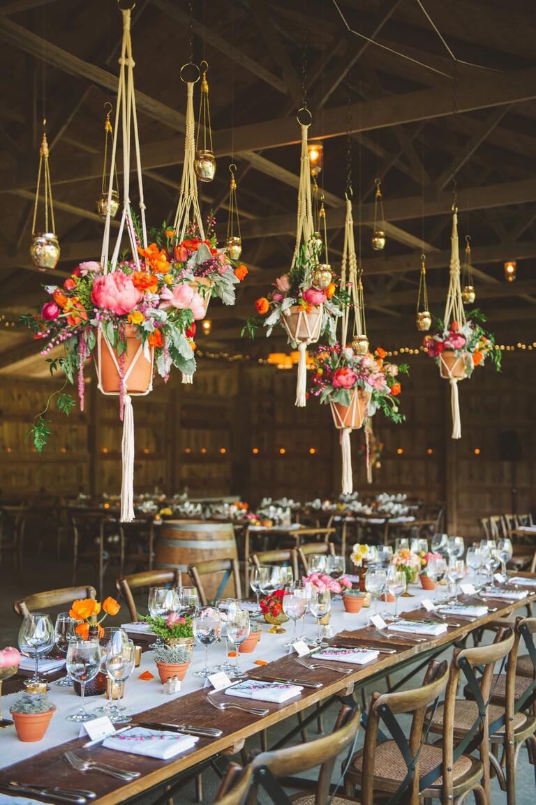 Suspended floral arrangements in a barn wedding reception