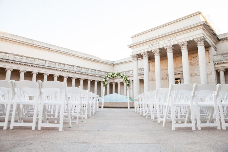 The ceremony took place at the outdoor Court of Honor site, where white folding chairs faced the white wedding arch decorated in ivory blooms and green lush foliage.