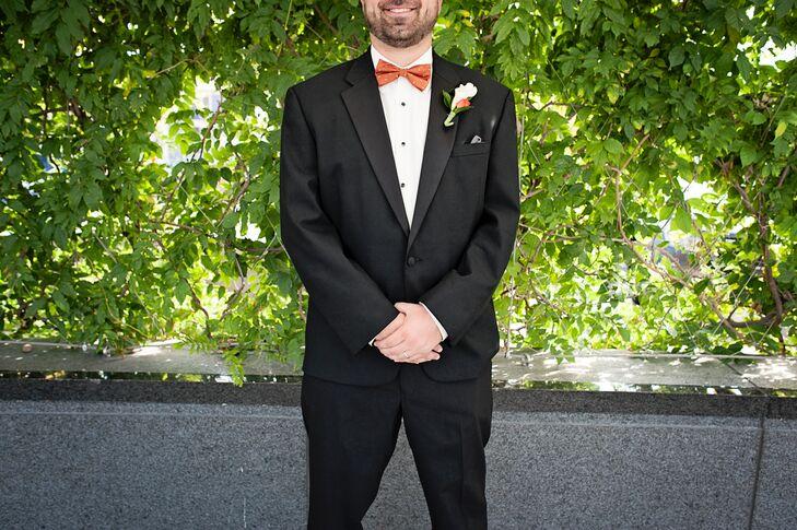 groom in black suit and orange bow tie