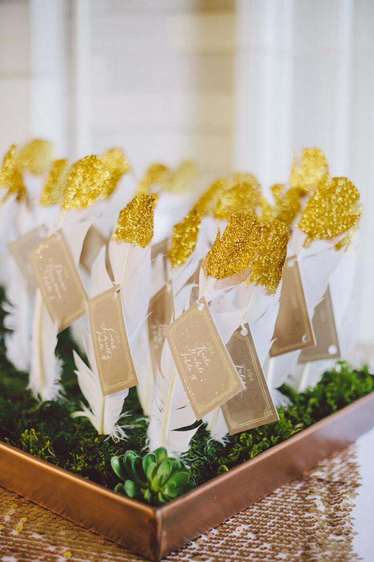 White escort card feathers with gold accent