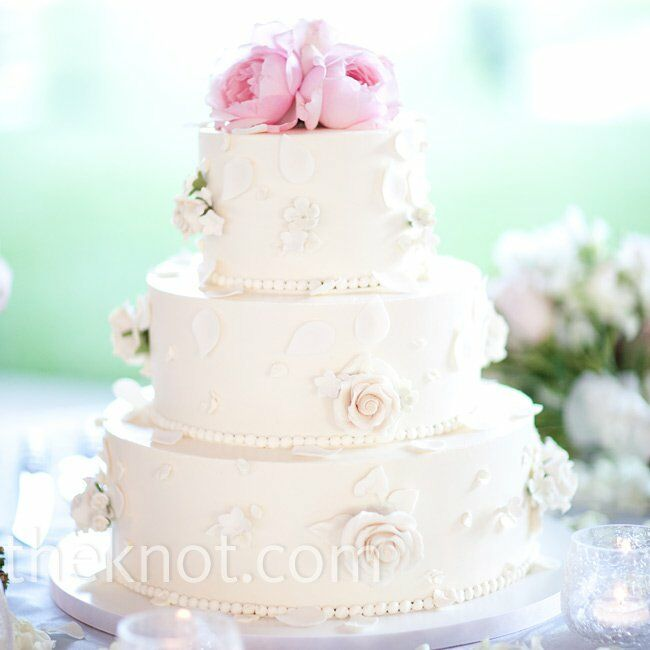 Handmade sugar flowers and rose petals decorated the couple's buttercream cake, which was topped with fresh, soft-pink roses.