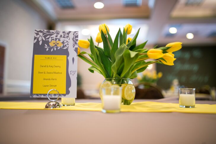 Centerpieces consisted of yellow bouquets with different flowers in vases filled with lemons. Table names and seating arrangements were displayed on gray and yellow signs that echoed the wedding invitations.