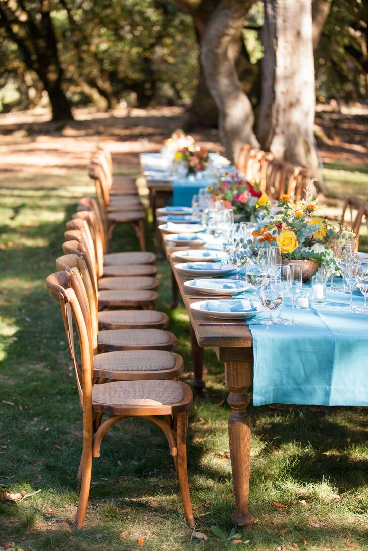 Bright teal table runners covered long wooden banquet tables at the outdoor reception and were topped with bright yellow and red blossoms—all keeping with the day's fire color spectrum.