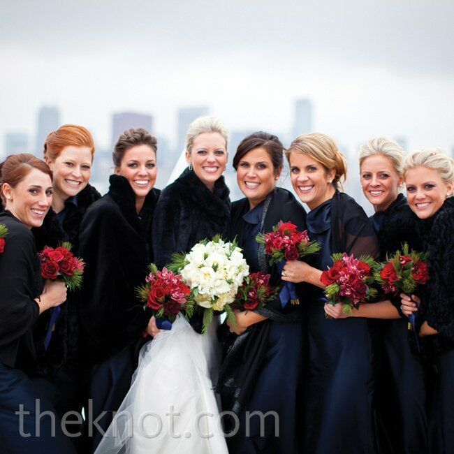 Katie's bridesmaids wore formal navy floor-length gowns topped off with black shawls or faux-fur jackets.