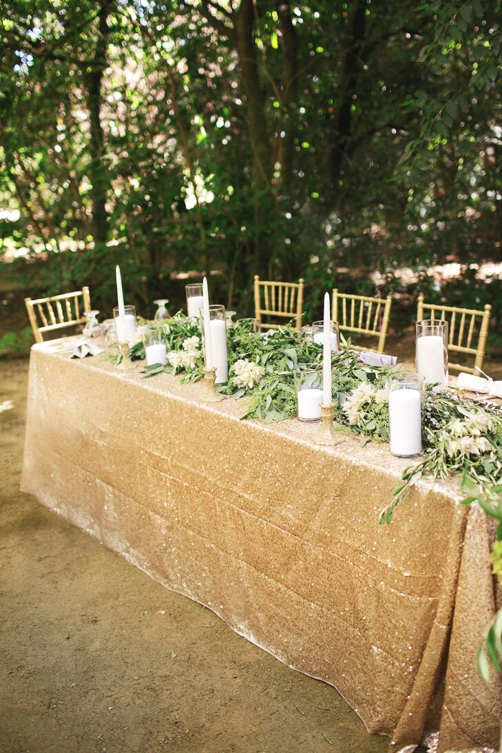 The long dining table was dressed in a gold sequin tablecloth, which had a lush garland made of leaves and white flowers draped down the middle. White, thin candlesticks, as well as thicker candles in glass cylinders, surrounded the garland for additional decor.
