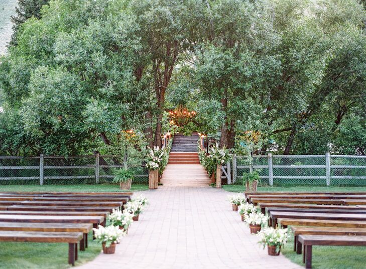 """We really live by the the ""less is more"" mentality which we wanted carried through to our wedding day to reflect us as a couple,"" Hayley says. The couple accented long wood benches at the ceremony space with potted florals."