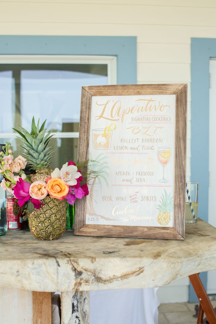 A preview for the fruit escort cards at the reception, they accented a signature-drink sign from PaperTangent with an actual pineapple. Bright garden roses, roses, orchids, delphiniums and lisianthus stemmed from the gold fruit, bringing out their bright color scheme.