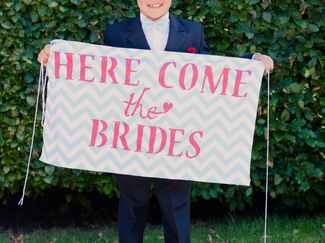 "Ring bearer holding ""Here Come the Brides"" sign for ceremony processional"
