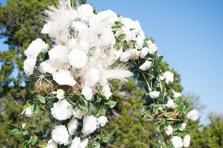 The couple got married under a lush arch of white flowers and feathers.