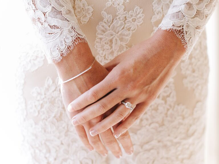 bride with a diamond engagement ring and a lace wedding dress - Wedding Rings On Hands