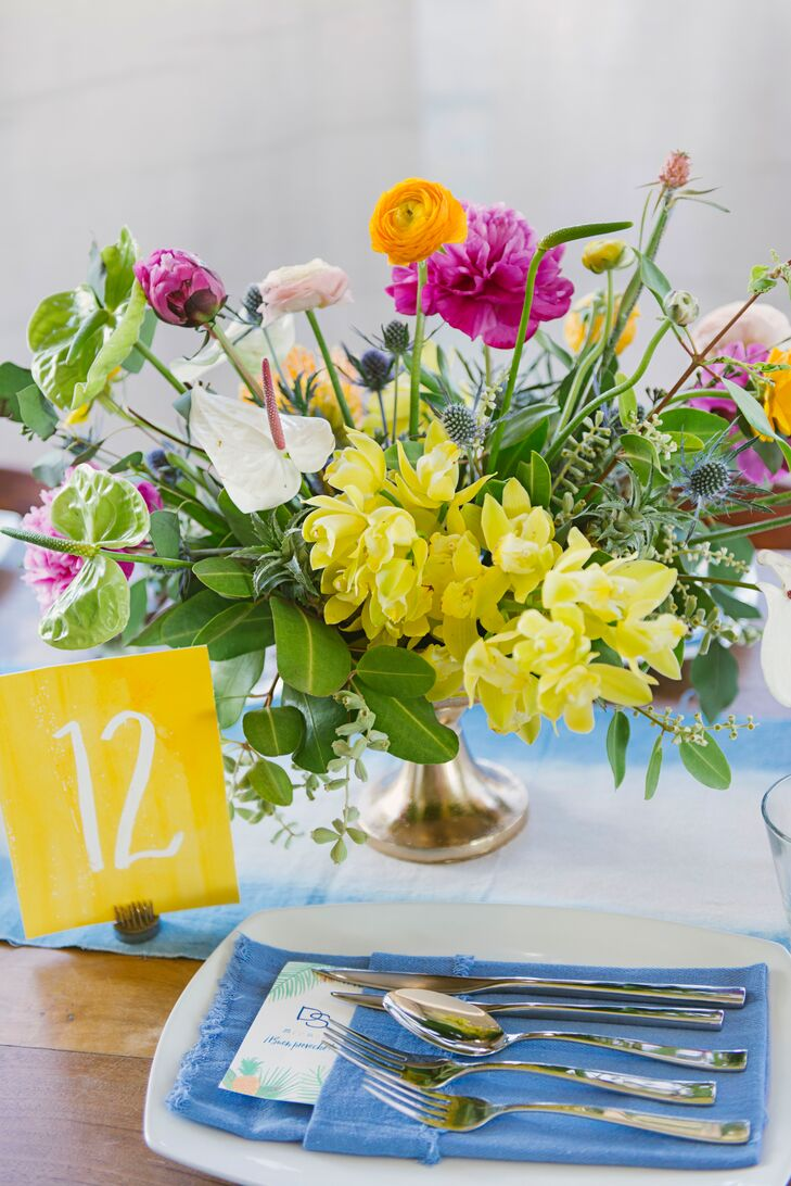 "The day's tropical-inspired palette was reflected in bright yellow place cards, blue hand-dyed linens, dip-dyed tablecloths and napkins. ""It all went along with the watercolor-based design used throughout our stationery and other paper goods,"" Diana says."