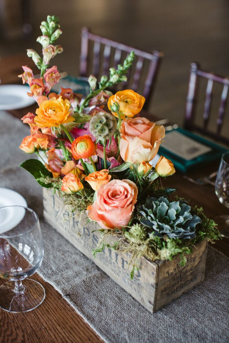 Centerpieces were made with a mix of succulents and orange and peach roses.  The antique wooden boxes were found by family and friends at local yard sales throughout the couple's engagement.