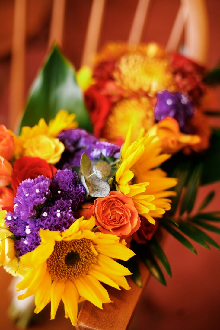 Charmagne and Tianna carried bouquets of yellow sunflowers, red, burnt orange and yellow roses and purple flowers on their fall wedding day.