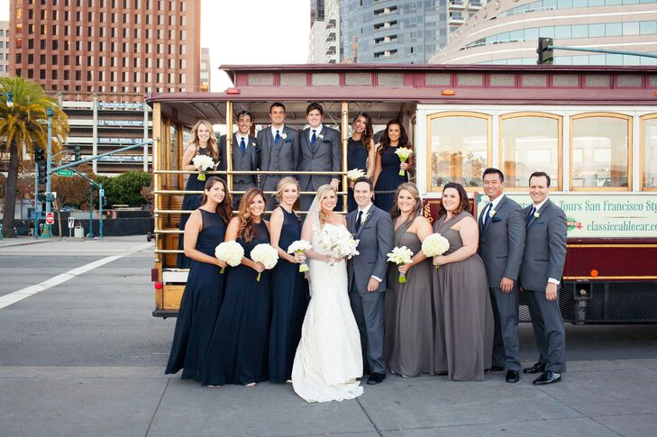 Courtney and Patrick stood with their wedding party dressed in blue and gray accents and posed around a trolley car. Bridesmaids wore midnight blue or charcoal long dresses in different styles, while the groomsmen matched Patrick with charcoal gray suits.