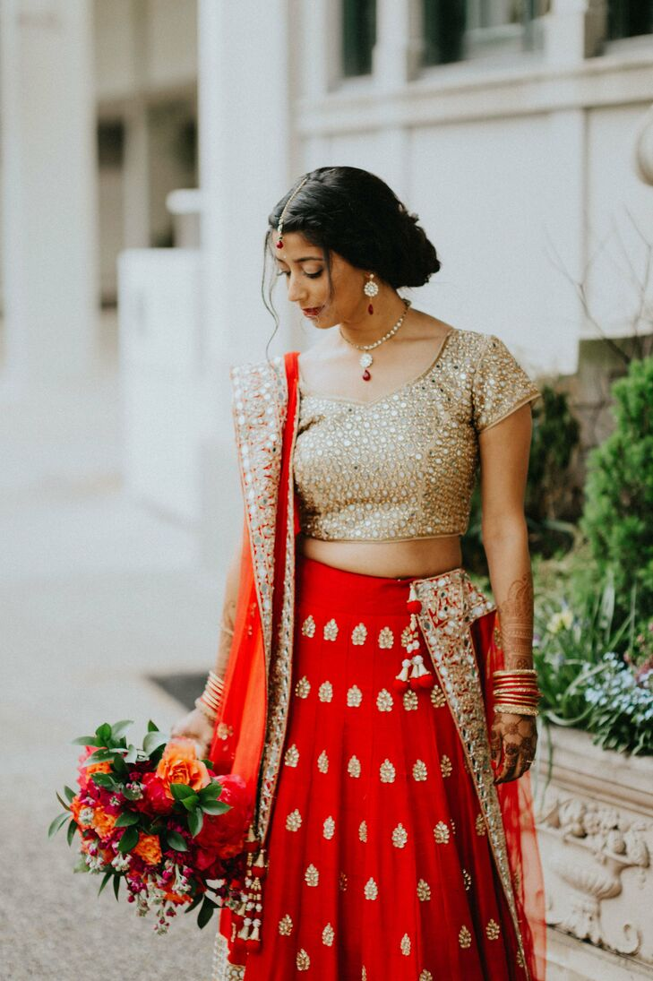 "When it came to her ""I do"" attire, Anjali took the traditional route, donning a red and gold panetar sari in red and gold. The lengha featured subtle pleating and a gold motif for a modern look, which she paired with a gold blouse embellished with mirrored details."
