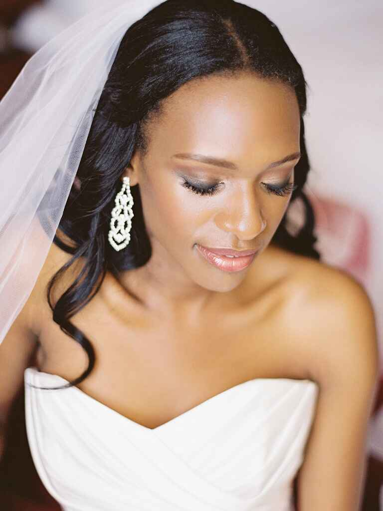 A bride with glowing skin and smoky eyes wearing chandelier earrings looking down