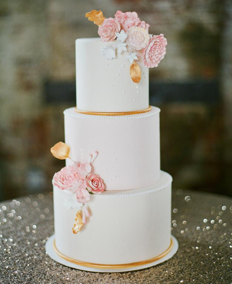 Ivory, gold, and blush wedding cake with sugar flowers and swiss dot decorations
