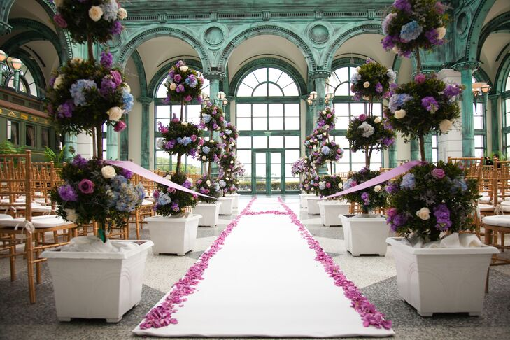 "The couple decorated their wedding with ten arrangements of three-tier manicured bushes accented with purple, ivory and pink roses as well as blue hydrangea. The aisle was also trimmed with pink flower petals in the shape of an ""H."""