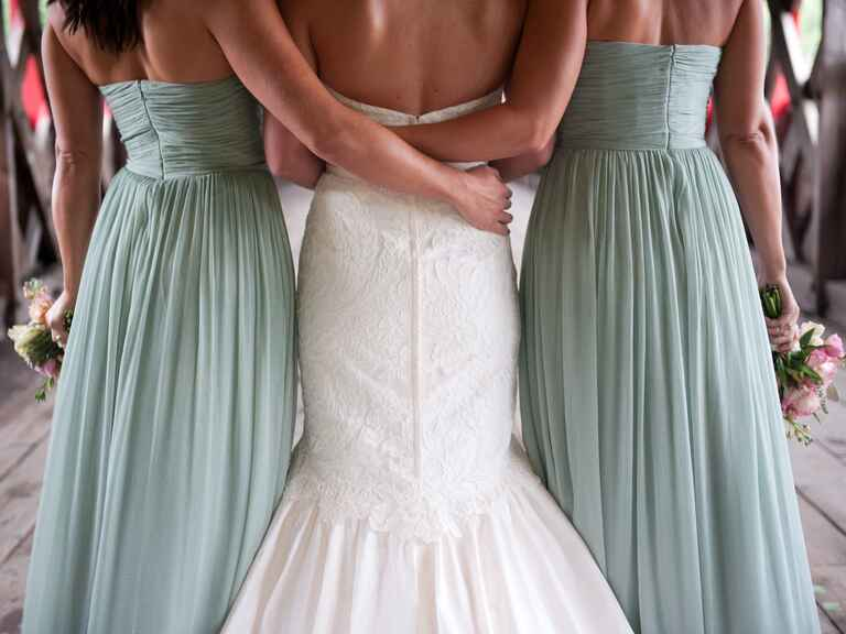 Two bridesmaids with their arms around the bride
