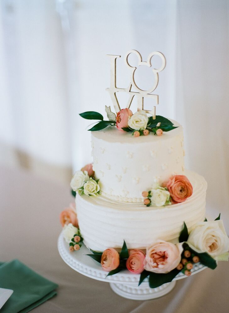 "Jamie and Alex's whimsical ""love"" cake topper incorporated Mickey Mouse and a cat. ""We love our cat, and he has really made us feel like a family the last two years,"" Jamie says. ""We couldn't take him to Maine with us but wanted him represented at the wedding."""