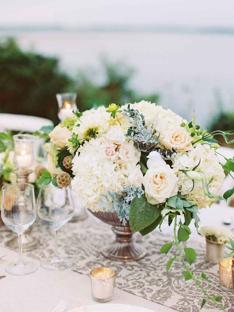 Lush white centerpieces of hydrangea, roses, and natural greenery