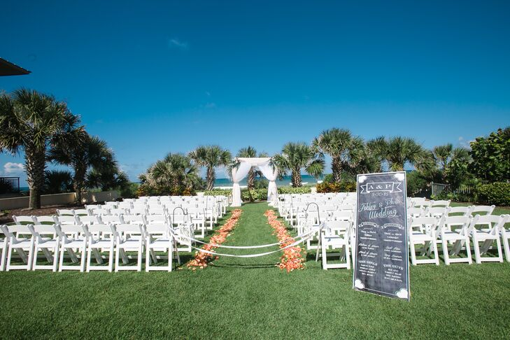 "Ashley and Phil loved the idea of a beach-chic wedding. So they took advantage of the Hammock Beach Resort's waterfront ceremony space in Palm Coast, Florida, and highlighted the entire setting with white and orange decor. Orange and white flower petals lined rows of white folding chairs toward the beach. A chalkboard wedding program also marked the front. ""The chalkboard sign was very special,"" Ashley says. ""It will hang in our new house this fall."""