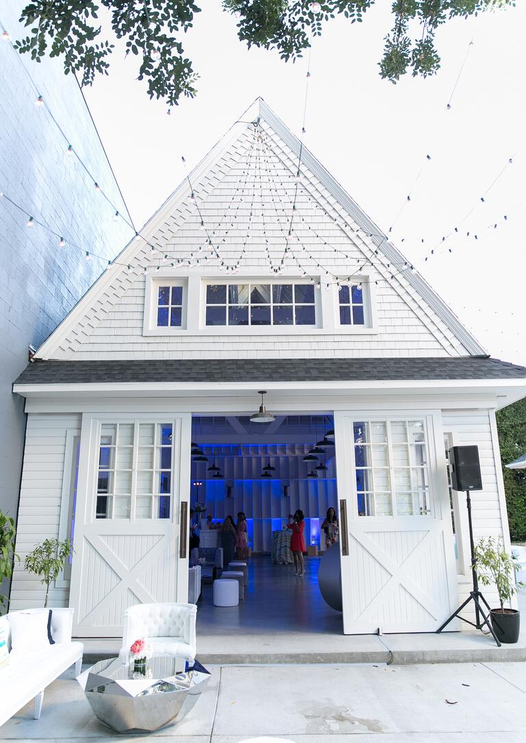 White barn venue with string lights