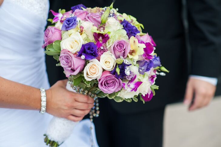 Tiffany carried a lush rose and iris bouquet incorporating shades of ivory and purple. She wrapped the arrangement in a swatch of lace and added her rosary beads for a sentimental and spiritual touch.