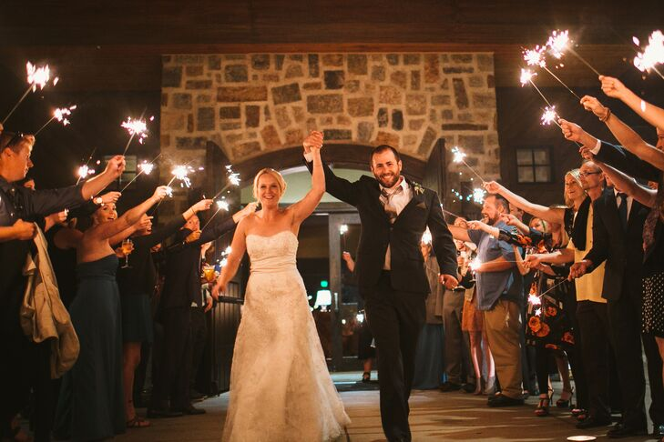 Bethany and Lucas raised their hands as they exited the reception for the evening, with friends and family paving the way and holding sparklers to celebrate their marriage. Lucas wore a charcoal JoS. A. Bank suit paired with a silver tie.