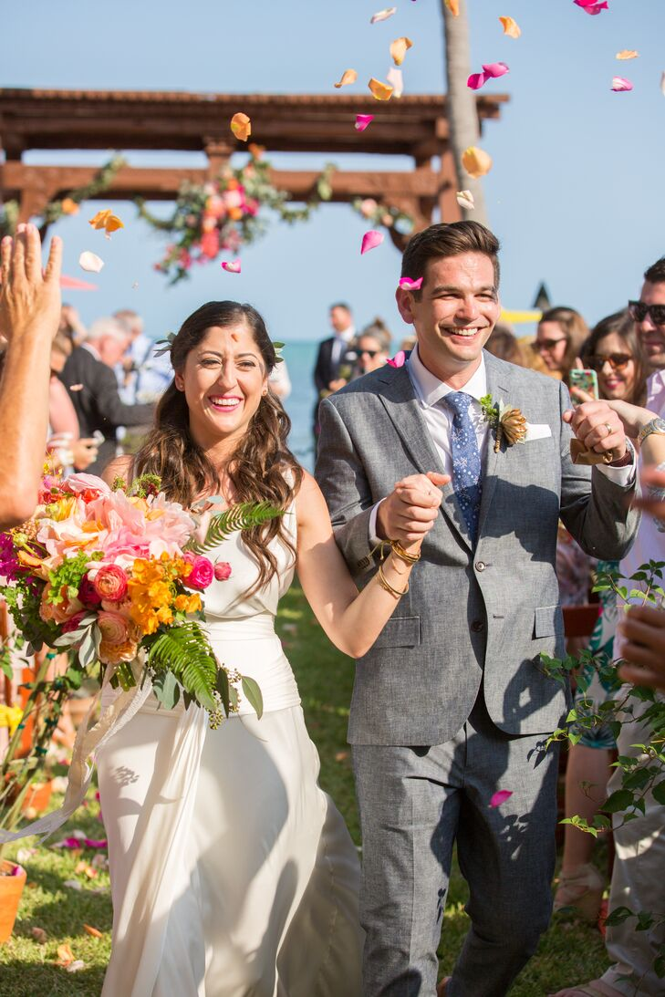 When Francesca and Michael met with a planner from Flutter Fete, one of their requirements was that their wedding had to be filled with vibrant colors. Their recessional was no exception. Francesca and Michael held hands through a cloud of bright orange, white and fuchsia rose petals as walked up the aisle.