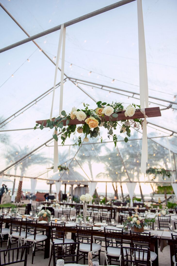 String lights illuminated the clear tent while arrangements of lush peonies, roses and eucalyptus hung from the rods by thick ivory ribbon.