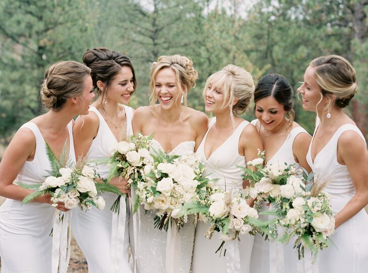 The bridesmaids wore off-white floor-length gowns with sweetheart necklines and form-fitting silhouettes.