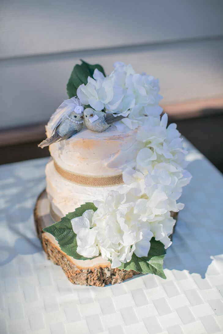 Hydrangeas decorated the two-tier ivory wedding cake from top to bottom, with two birds topping the dessert. A wooden slab under the cake added a natural touch.