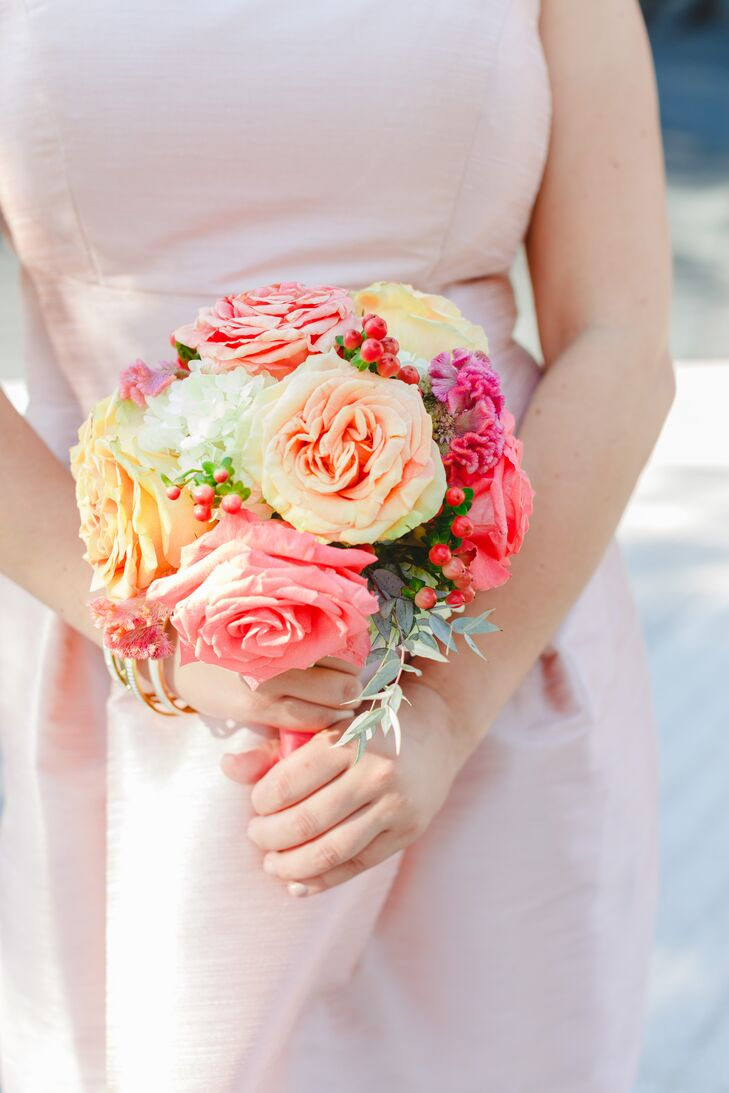 The bridesmaids held a colorful assortment of roses and peonies accented with berries in their bouquet.