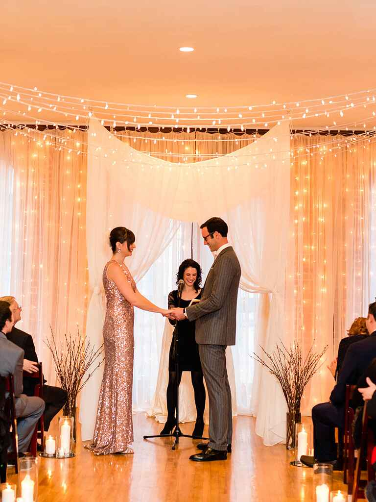 Inspiration to brighten up any indoor ceremony with string lights and translucent draped curtains