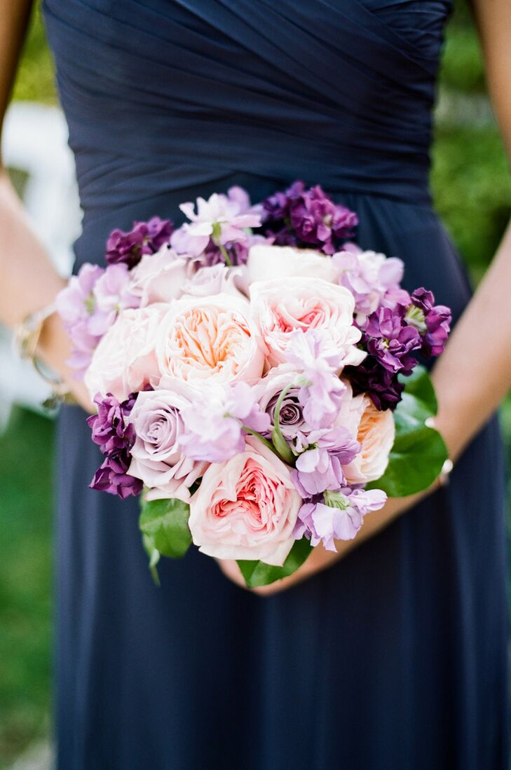 Playing off Ashley's bridal bouquet, Enchanted Florist Nashville created bright, romantic arrangements with a garden-inspired twist for the bridesmaids. The full pink and purple garden roses and stock tied into the wedding's color scheme seamlessly and popped against the girls' sophisticated navy chiffon gowns.