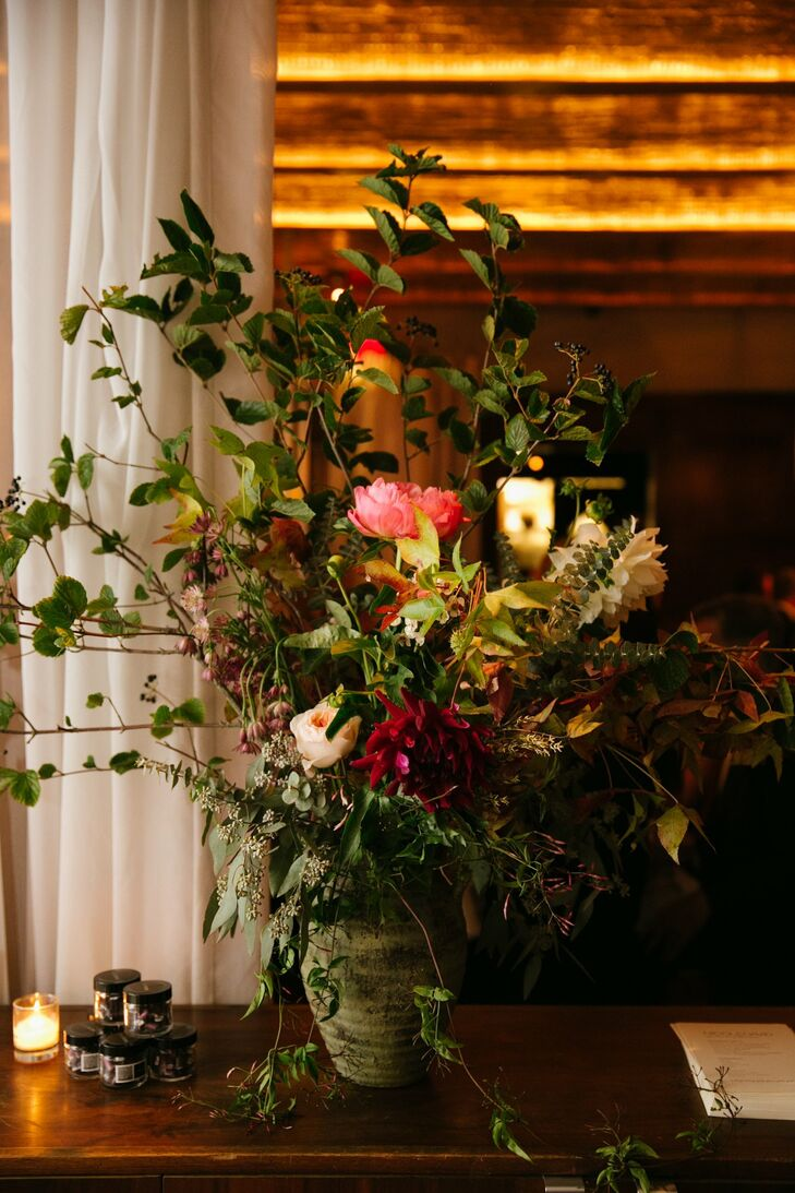 The oversize centerpieces featured lush greenery, complemented by pink peonies and dark red dahlias.