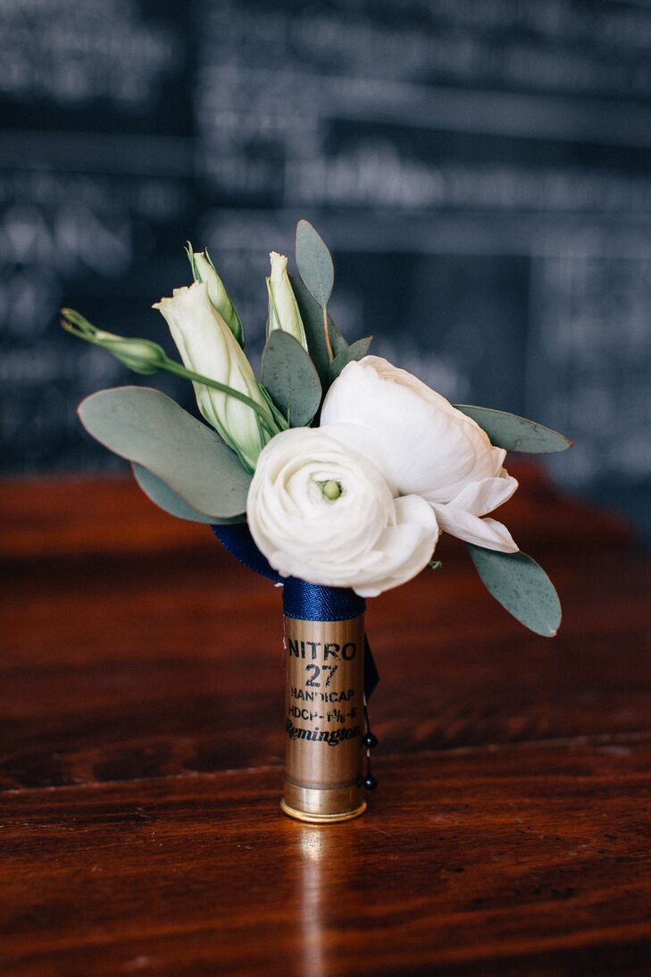 The groomsmen wore gold shotgun-shell boutonnieres with white ranunculus and eucalyptus.